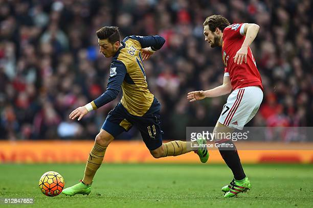 Mesut Oezil of Arsenal goes past Daley Blind of Manchester United during the Barclays Premier League match between Manchester United and Arsenal at...