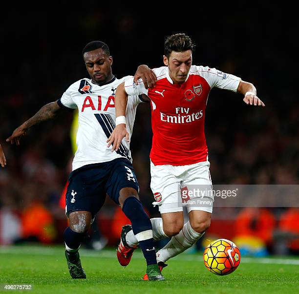 Mesut Oezil of Arsenal holds off Danny Rose of Spurs during the Barclays Premier League match between Arsenal and Tottenham Hotspur at the Emirates...