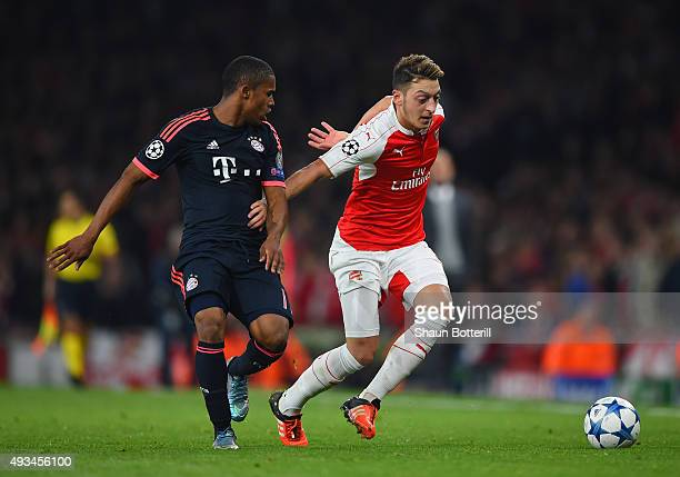 Mesut Oezil of Arsenal holds off Douglas Costa of Bayern Munich during the UEFA Champions League Group F match between Arsenal FC and FC Bayern...