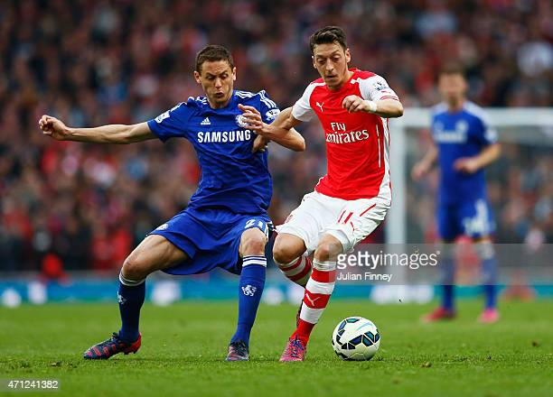 Mesut Oezil of Arsenal holds off Nemanja Matic of Chelsea during the Barclays Premier League match between Arsenal and Chelsea at Emirates Stadium on...