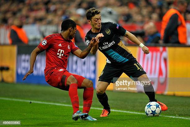 Mesut Oezil of Arsenal holds off the challenge from Douglas Costa of Bayern Muenchen during the UEFA Champions League Group F match between FC Bayern...