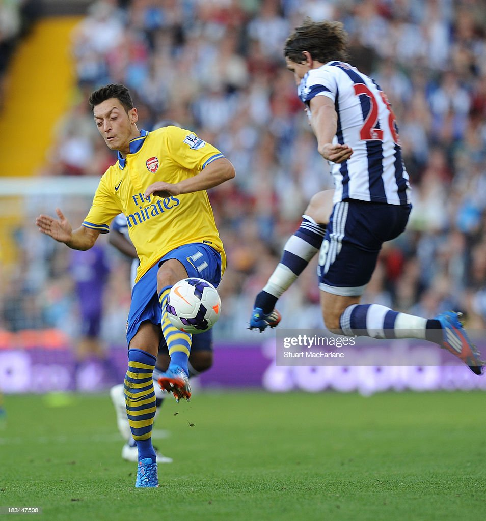 <a gi-track='captionPersonalityLinkClicked' href=/galleries/search?phrase=Mesut+Oezil&family=editorial&specificpeople=764075 ng-click='$event.stopPropagation()'>Mesut Oezil</a> of Arsenal in action against Billy Jones of West Bromwich Albion during the Barclays Premier League match between West Bromwich Albion and Arsenal FC at The Hawthorns on October 6, 2013 in West Bromwich, England.