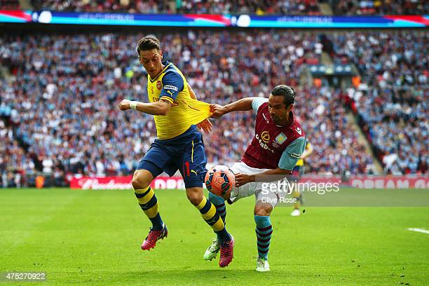 Mesut Oezil of Arsenal is challenged by Kieran Richardson of Aston Villa during the FA Cup Final between Aston Villa and Arsenal at Wembley Stadium...