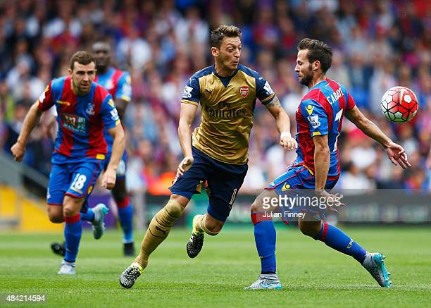 Mesut Oezil of Arsenal is challenged by Yohan Cabaye of Crystal Palace during the Barclays Premier League match between Crystal Palace and Arsenal at...
