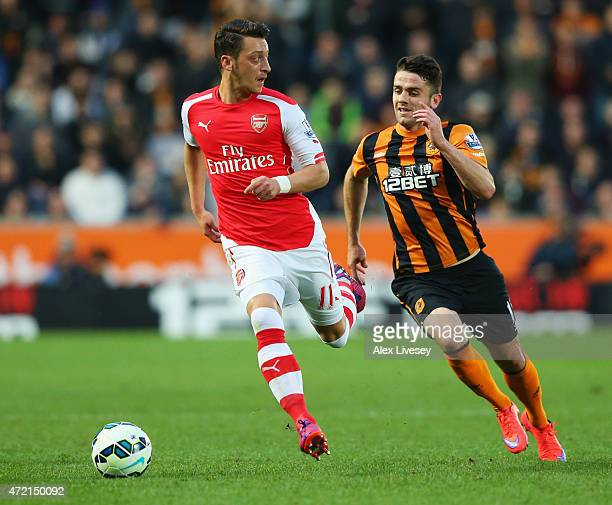 Mesut Oezil of Arsenal is chased by Robbie Brady of Hull City during the Barclays Premier League match between Hull City and Arsenal at KC Stadium on...