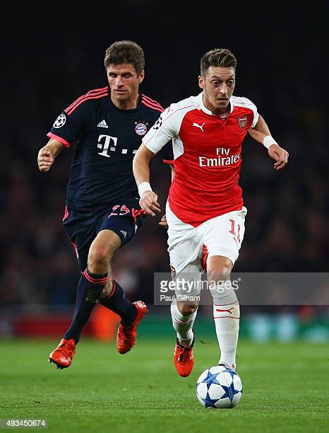 Mesut Oezil of Arsenal is chased by Thomas Mueller of Bayern Munich during the UEFA Champions League Group F match between Arsenal FC and FC Bayern...