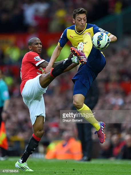 Mesut Oezil of Arsenal jumps for the ball with Ashley Young of Manchester United during the Barclays Premier League match between Manchester United...