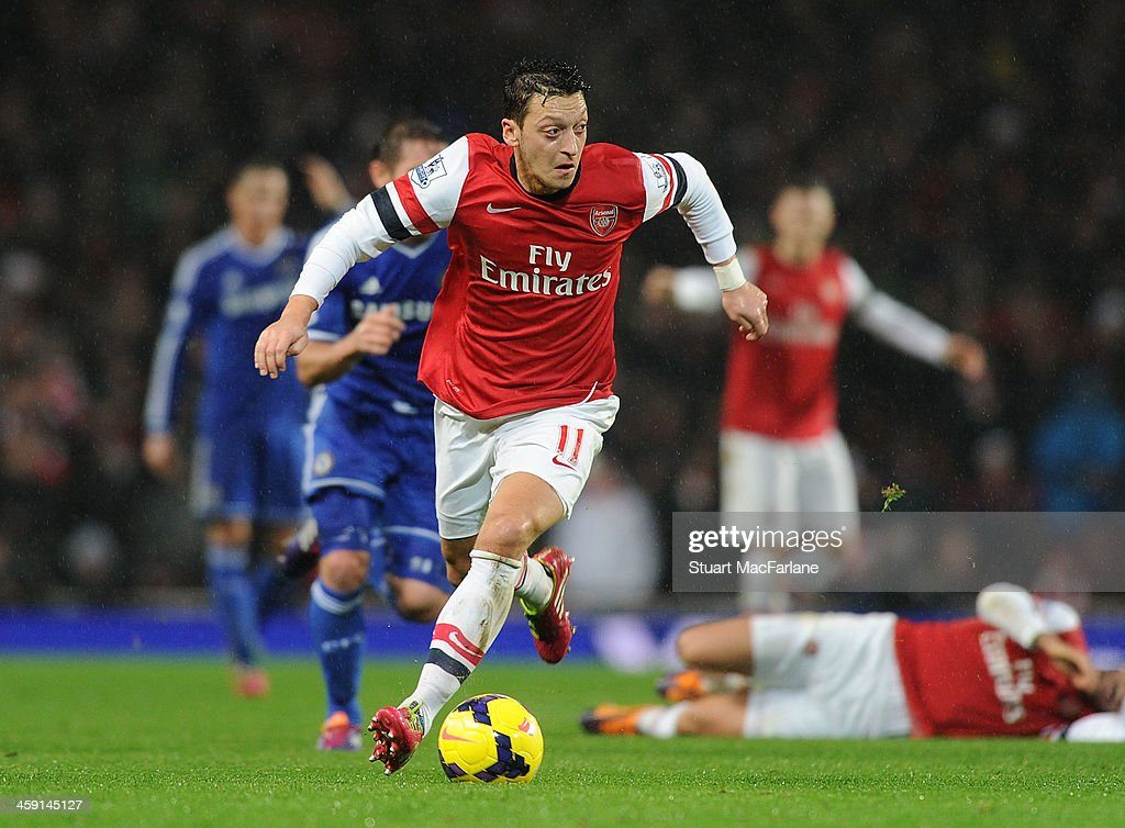 Mesut Oezil of Arsenal runs with the ball during the match at Emirates Stadium on December 23, 2013 in London, England.