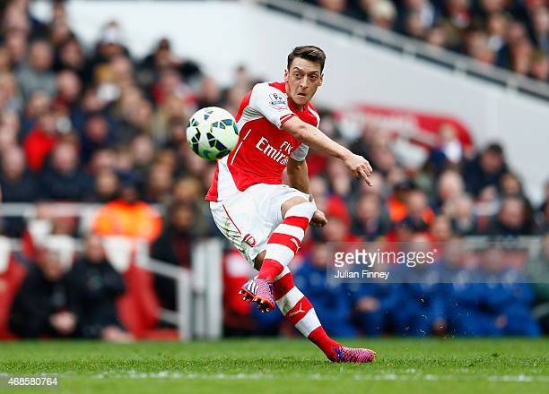 Mesut Oezil of Arsenal scores his team's second goal from a freekick during the Barclays Premier League match between Arsenal and Liverpool at...
