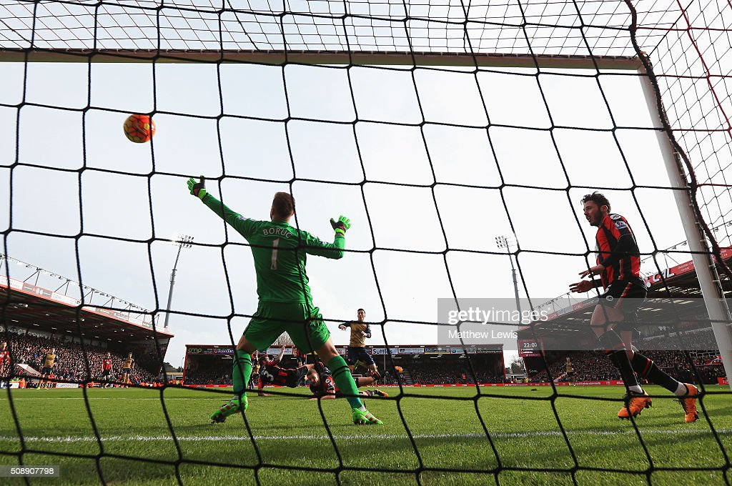 Mesut Oezil of Arsenal (c) shoots past goalkeeper Artur Boruc of Bournemouth to score their first goal during the Barclays Premier League match between A.F.C. Bournemouth and Arsenal at the Vitality Stadium on February 7, 2016 in Bournemouth, England.