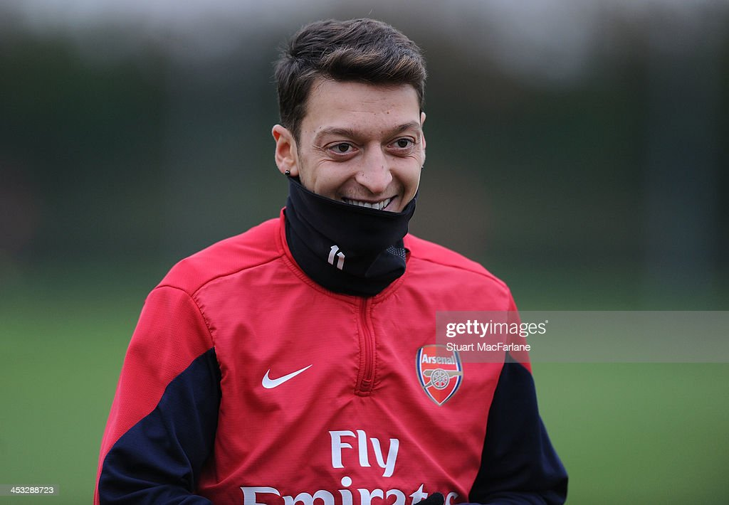 Mesut Oezil of Arsenal smiles during a training session at London Colney on December 3, 2013 in St Albans, England.