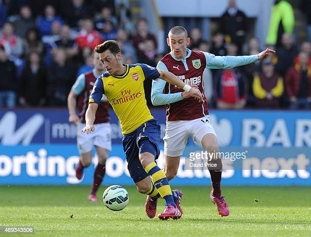 Mesut Oezil of Arsenal takes on David Jones of Burnley during the Barclays Premier League match between Burnley and Arsenal at Turf Moor on April 11...