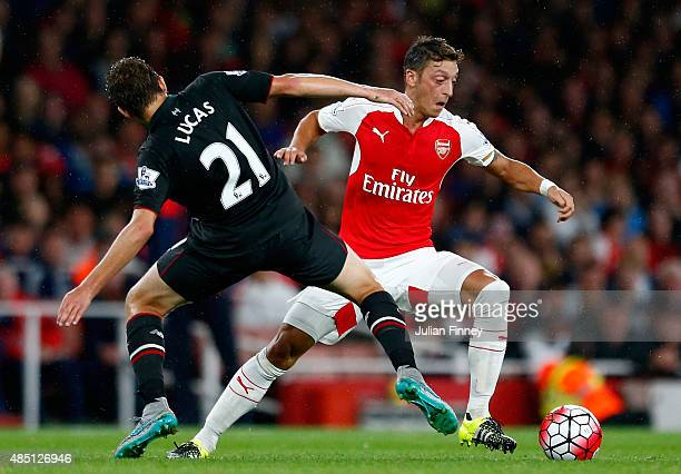 Mesut Oezil of Arsenal takes on Lucas Leiva of Liverpool during the Barclays Premier League match between Arsenal and Liverpool at the Emirates...