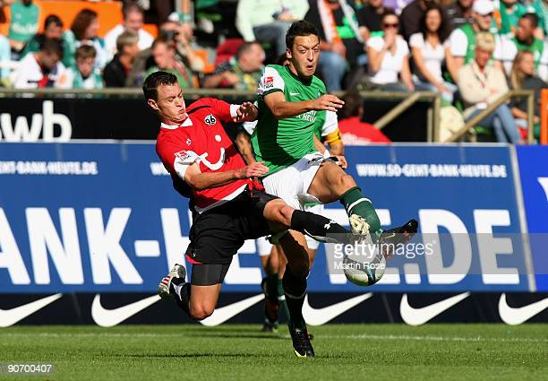 Mesut Oezil of Bremen and Hanno Balitsch of Hannover battle for the ball during the Bundesliga match between Werder Bremen and Hannover 96 at the...