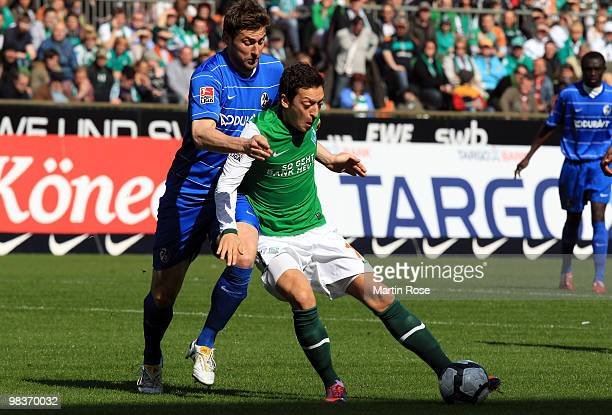 Mesut Oezil of Bremen and Heiko Butscher of Freiburg compete for the ball during the Bundesliga match between Werder Bremen and SC Freiburg at the...