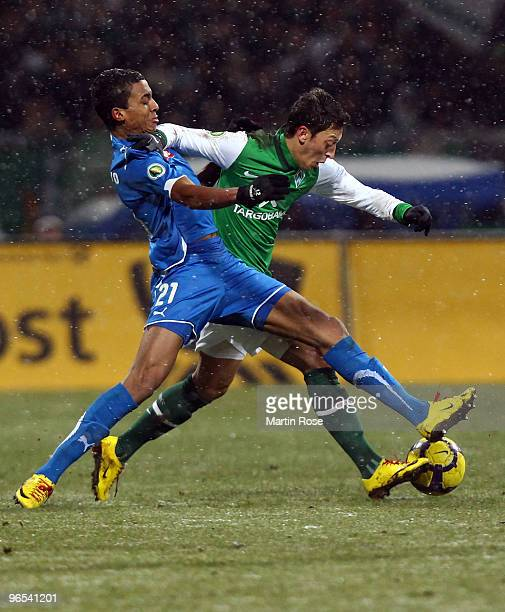 Mesut Oezil of Bremen and Luiz Gustavo of Hoffenheim battle for the ball during the DFB Cup quarter final match between SV Werder Bremen and 1899...