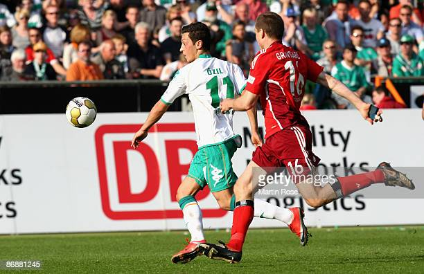 Mesut Oezil of Bremen and Michael Gravgaard of Hamburg compete for the ball during the Bundesliga match between Werder Bremen and Hamburger SV at the...
