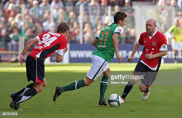 Mesut Oezil of Bremen Konstantin Rausch and Jiri Stajner of Hannover battle for the ball during the Bundesliga match between Werder Bremen and...