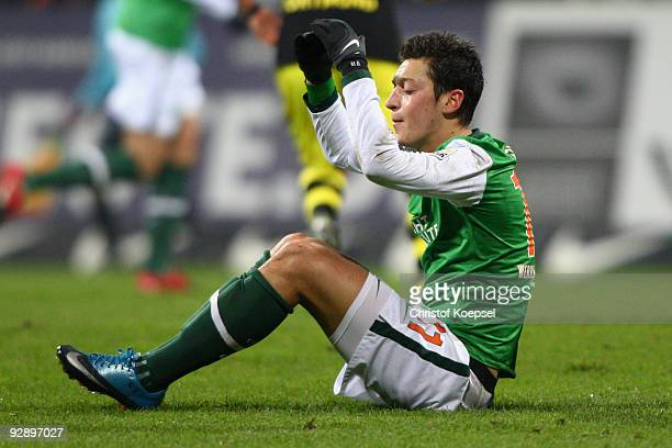 Mesut Oezil of Bremen sits dejected on the pitch during the Bundesliga match between SV Werder Bremen and Borussia Dortmund at the Weser Stadium on...