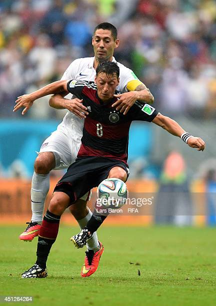 Mesut Oezil of Germany and Clint Dempsey of the United States compete for the ball during the 2014 FIFA World Cup Brazil Group G match between USA...
