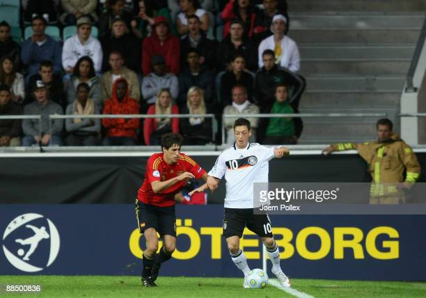 Mesut Oezil of Germany and Javi Martinez of Spain battle for the ball during the UEFA U21 Championship Group B match between Spain and Germany at the...
