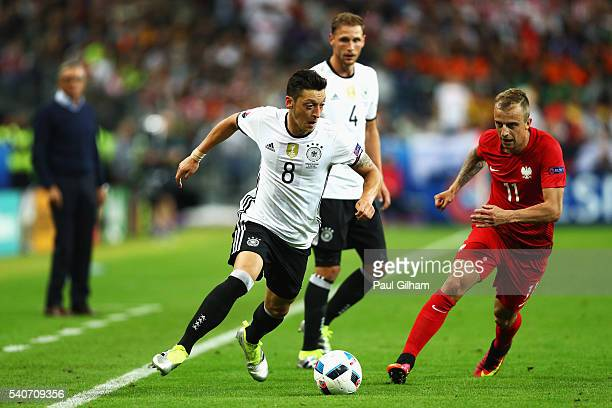 Mesut Oezil of Germany and Kamil Grosicki of Poland compete for the ball during the UEFA EURO 2016 Group C match between Germany and Poland at Stade...