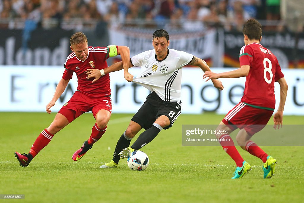 Mesut Oezil of Germany battles for the ball with Balazs Dzudszak of Hungary and his team mate Adam Nagy during the international friendly match...