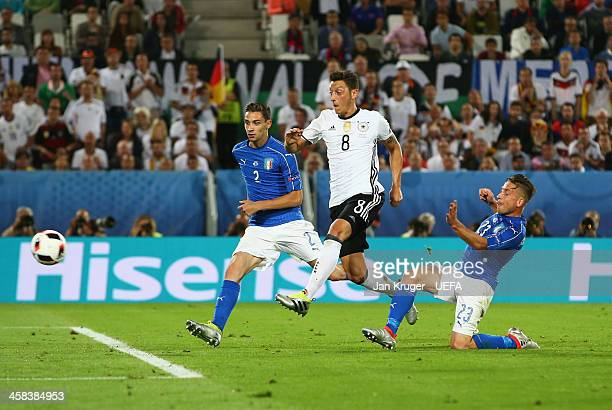 Mesut Oezil of Germany beats Mattia De Sciglio and Emanuele Giaccherini of Italy to score their first goal during the UEFA EURO 2016 quarter final...