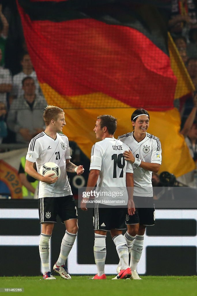 <a gi-track='captionPersonalityLinkClicked' href=/galleries/search?phrase=Mesut+Oezil&family=editorial&specificpeople=764075 ng-click='$event.stopPropagation()'>Mesut Oezil</a> (R) of Germany celebrates scoring the second team goal with his team mates <a gi-track='captionPersonalityLinkClicked' href=/galleries/search?phrase=Mario+Goetze&family=editorial&specificpeople=4251202 ng-click='$event.stopPropagation()'>Mario Goetze</a> (C) and <a gi-track='captionPersonalityLinkClicked' href=/galleries/search?phrase=Marco+Reus&family=editorial&specificpeople=5445884 ng-click='$event.stopPropagation()'>Marco Reus</a> during the FIFA 2014 World Cup Qualifier group C match between Germany and Faeroe Islands at AWD Arena on September 7, 2012 in Hanover, Germany.