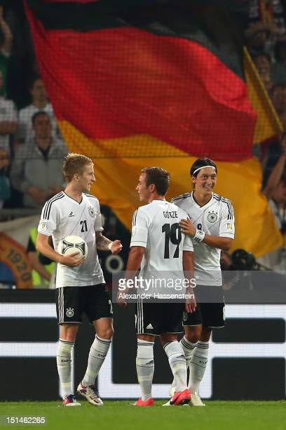 Mesut Oezil of Germany celebrates scoring the second team goal with his team mates Mario Goetze and Marco Reus during the FIFA 2014 World Cup...