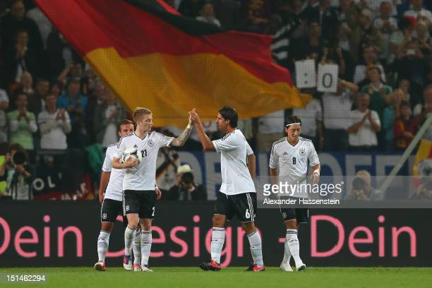 Mesut Oezil of Germany celebrates scoring the second team goal with his team mates Mario Goetze and Marco Reus and Sami Khedira during the FIFA 2014...