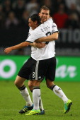 Mesut Oezil of Germany celebrates the first goal with Per Mertesacker during the UEFA EURO 2012 Group A qualifying match between Germany and Belgium...