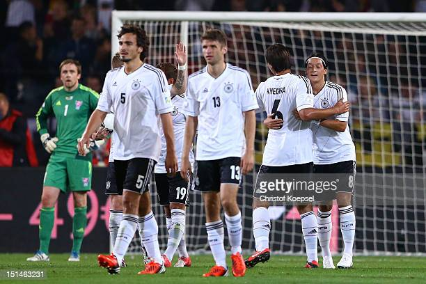 Mesut Oezil of Germany celebrates the second goal with Sami Khedira during the FIFA 2014 World Cup Qualifier group C match between Germany and Faeroe...