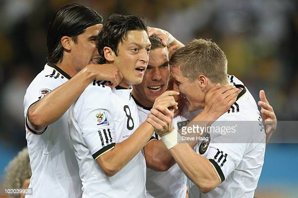 Mesut Oezil of Germany celebrates with goalscorer Lukas Podolski during the 2010 FIFA World Cup South Africa Group D match between Germany and...