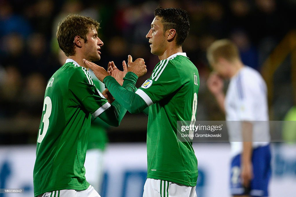 Mesut Oezil of Germany celebrates with teammate Thomas Mueller after scoring his team's second goal during the FIFA 2014 World Cup Qualifier match between Faeroe Islands and Germany on September 10, 2013 in Torshavn, Denmark.