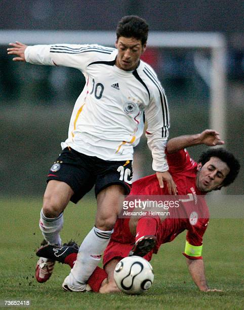 Mesut Oezil of Germany competes with Mirza Bzhalava of Georgia during the Men's U19 international friendly match between Germany and Georgia on March...