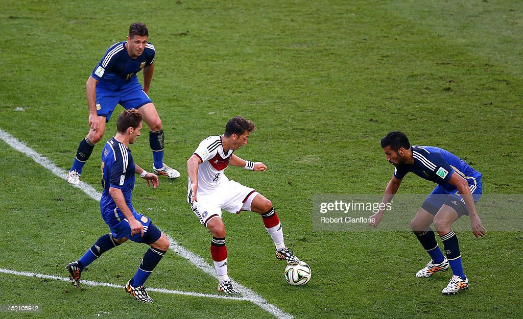Mesut Oezil of Germany controls the ball against Lucas Biglia, Martin Demichelis and Ezequiel Garay of Argentina during the 2014 FIFA World Cup Brazil Final match between Germany and Argentina at Maracana on July 13, 2014 in Rio de Janeiro, Brazil.
