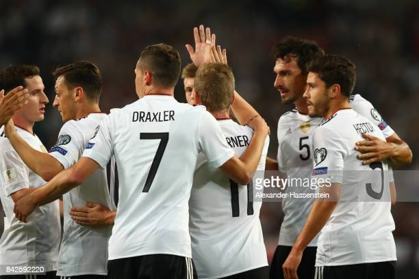 Mesut Oezil of Germany is celebrated by Julian Draxler of Germany and Jonas Hector of Germany after he scored Germany's first goal during the FIFA...