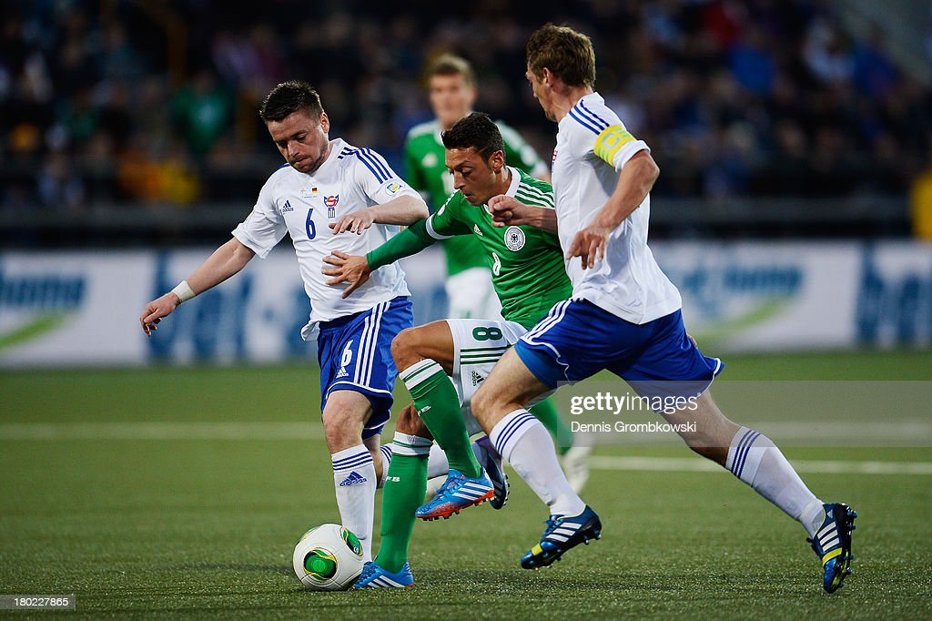 Mesut Oezil of Germany is challenged by Suni Olsen of Faeroe Islands during the FIFA 2014 World Cup Qualifier match between Faeroe Islands and Germany on September 10, 2013 in Torshavn, Denmark.