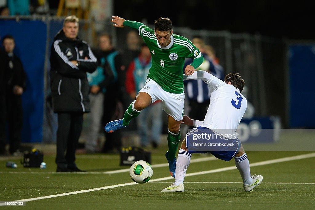 Mesut Oezil of Germany is challenged by Viljormur Davidsen of Faeroe Islands during the FIFA 2014 World Cup Qualifier match between Faeroe Islands and Germany on September 10, 2013 in Torshavn, Denmark.