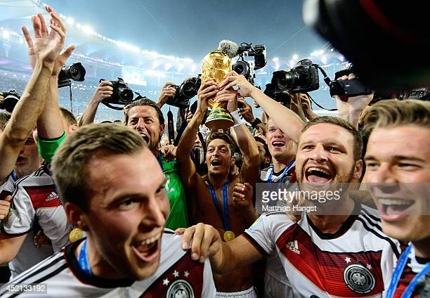 Mesut Oezil of Germany raises the World Cup trophy with teammates Kevin Grosskreutz Roman Weidenfeller Shkodran Mustafi and Erik Durm after defeating...