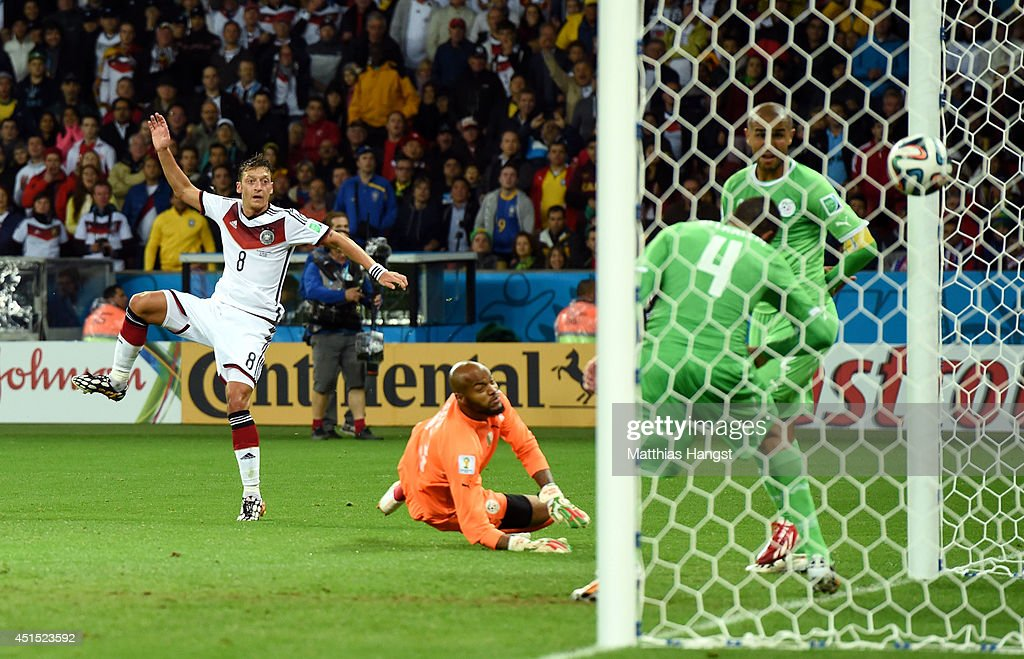 <a gi-track='captionPersonalityLinkClicked' href=/galleries/search?phrase=Mesut+Oezil&family=editorial&specificpeople=764075 ng-click='$event.stopPropagation()'>Mesut Oezil</a> of Germany scores his team's second goal past Rais M'Bolhi of Algeria during the 2014 FIFA World Cup Brazil Round of 16 match between Germany and Algeria at Estadio Beira-Rio on June 30, 2014 in Porto Alegre, Brazil.