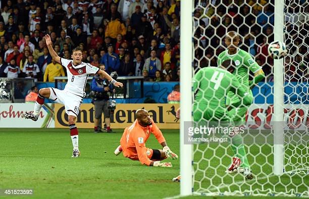 Mesut Oezil of Germany scores his team's second goal past Rais M'Bolhi of Algeria during the 2014 FIFA World Cup Brazil Round of 16 match between...