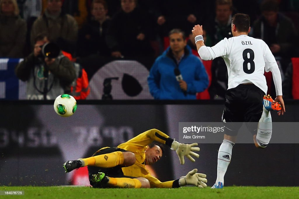 <a gi-track='captionPersonalityLinkClicked' href=/galleries/search?phrase=Mesut+Oezil&family=editorial&specificpeople=764075 ng-click='$event.stopPropagation()'>Mesut Oezil</a> of Germany scores his team's third goal against goalkeeper <a gi-track='captionPersonalityLinkClicked' href=/galleries/search?phrase=David+Forde+-+Soccer+Goalkeeper&family=editorial&specificpeople=1816778 ng-click='$event.stopPropagation()'>David Forde</a> of Ireland during the FIFA 2014 World Cup Group C qualifiying match between Germany and Republic of Ireland at RheinEnergieStadion on October 11, 2013 in Cologne, Germany.