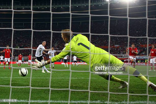 Mesut Oezil of Germany scores the 2nd team goal with a penalty kick against keeper Robert Almer of Austria during the FIFA 2014 World Cup Qualifier...