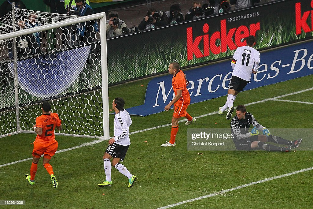 Mesut Oezil (L) of Germany scores the third goal against Gregory van der Wiel (L) Johnny Heitinga (3rd L) and Marteen Stekelenburg (2nd R) of Netherlands during the International Friendly match between Germany and Netherlands at Imtech Arena on November 15, 2011 in Hamburg, Germany.