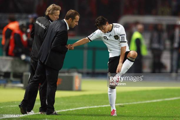 Mesut Oezil of Germany takes a look at his ankle with assistant coach hansDieter Flick after the EURO 2012 group A qualifier match between Germany...