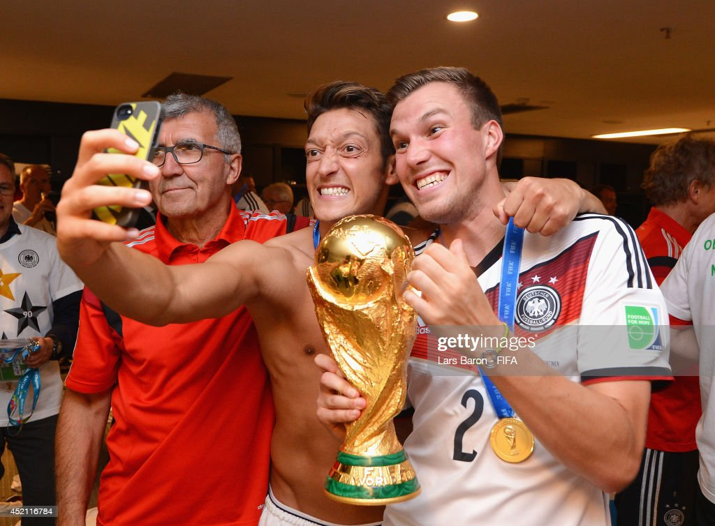 <a gi-track='captionPersonalityLinkClicked' href=/galleries/search?phrase=Mesut+Oezil&family=editorial&specificpeople=764075 ng-click='$event.stopPropagation()'>Mesut Oezil</a> of Germany (C) takes a photo of himself with <a gi-track='captionPersonalityLinkClicked' href=/galleries/search?phrase=Kevin+Grosskreutz&family=editorial&specificpeople=4265546 ng-click='$event.stopPropagation()'>Kevin Grosskreutz</a> of Germany and the World Cup trophy after the 2014 FIFA World Cup Brazil Final match between Germany and Argentina at Maracana on July 13, 2014 in Rio de Janeiro, Brazil.
