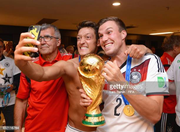 Mesut Oezil of Germany takes a photo of himself with Kevin Grosskreutz of Germany and the World Cup trophy after the 2014 FIFA World Cup Brazil Final...