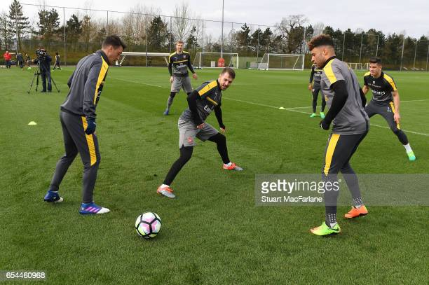 Mesut Ozil Aaron Ramsey and Alex OxladeChamberlain of Arsenal during a training session at London Colney on March 17 2017 in St Albans England